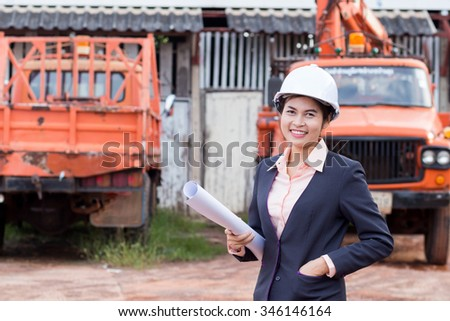 Beautiful female engineer holding blueprints in hand, On the background with trucks. - stock photo