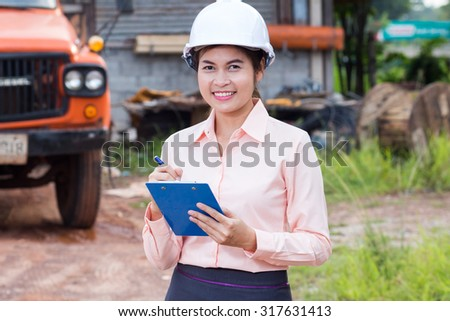 Beautiful female engineer wearing a helmet checking the list.
