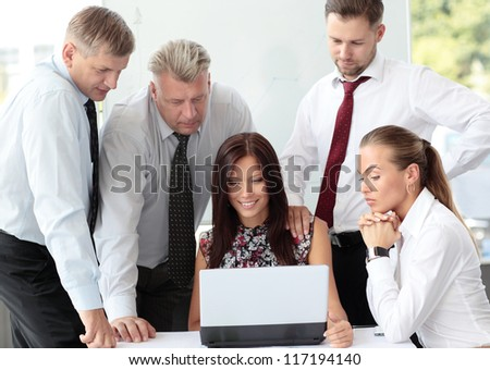 Beautiful female executive pointing at laptop screen while discussing business plan with colleagues - stock photo