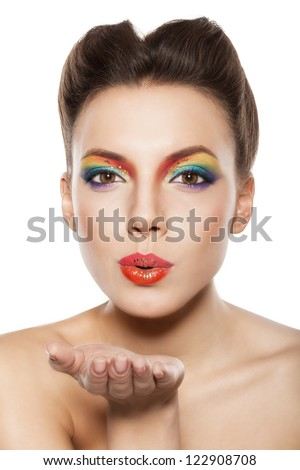 beautiful female face, rainbow makeup, girl blowing a kiss - stock photo