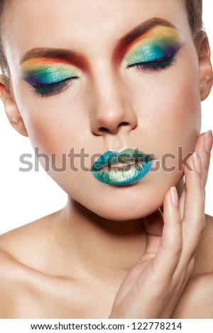 beautiful female face, rainbow makeup. girl witn closed eyes touch her face by hand - stock photo