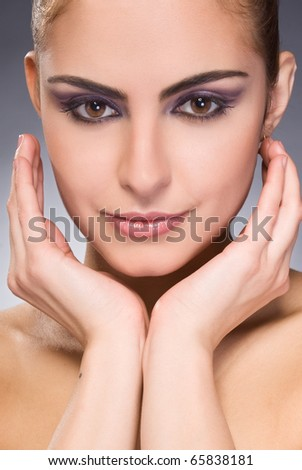 beautiful female face with make-up and hands on face looking on camera - stock photo