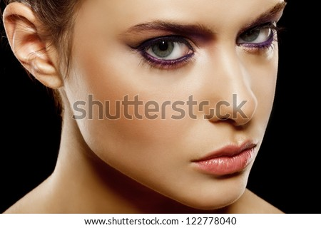 beautiful female face with natural makeup, on black background