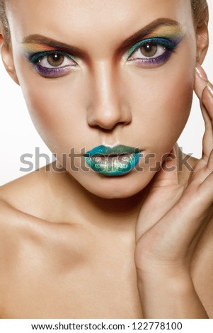 beautiful female face with rainbow makeup. girl touch her face by hand - stock photo