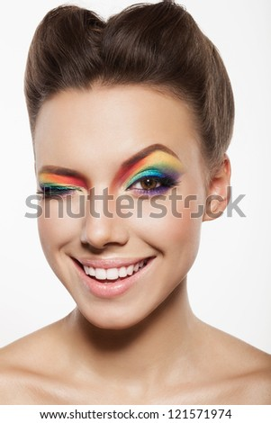 beautiful female face with rainbow makeup. girl winking and smiling - stock photo