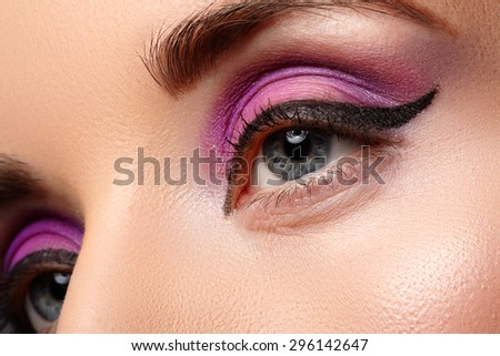 Beautiful female face with sexy black liner and bright purple makeup.