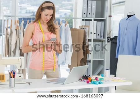 Beautiful female fashion designer using laptop and cellphone in the studio