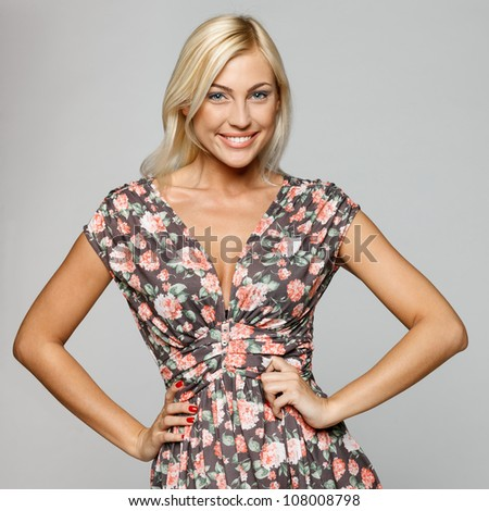 Beautiful female fashion model posing with hands on hips, over gray background