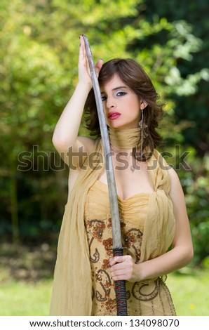 Beautiful female fighter with a sword in her hands. - stock photo