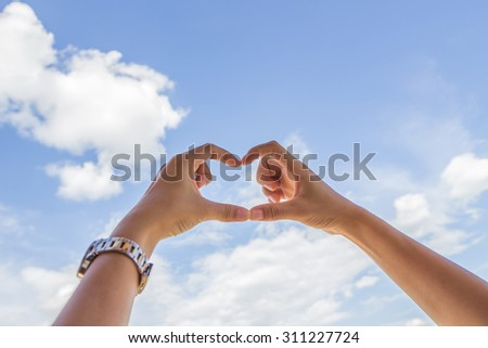 Beautiful female finger make shaping a heart symbol and blue sky background. - stock photo