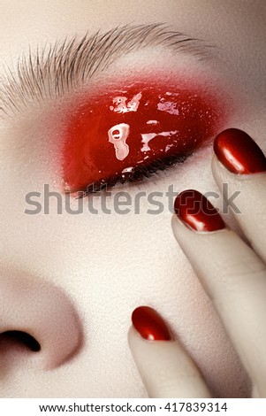 Beautiful female finger nails with red nail closeup on petals. Perfect manicure - stock photo