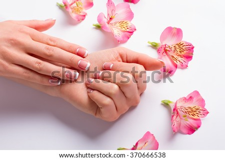 Beautiful female fingers with french manicure. Female hand with delicate flowers. - stock photo