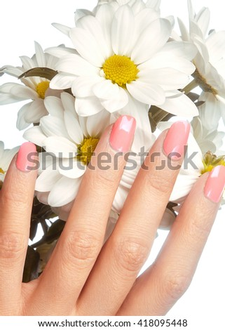 Beautiful female fingers with pastel pink manicure touching spring flowers. Care about female hands, healthy soft skin. Spa & cosmetics. Close-up of beautiful fingers with nails polish  - stock photo
