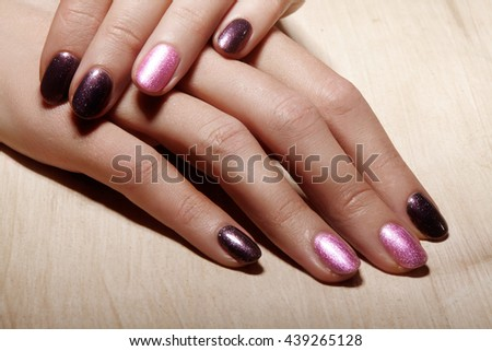 Beautiful female fingers with shiny gel manicure bright pink color. Holding nail polish bottle. Care about female hands, healthy soft skin. Spa & cosmetics - stock photo