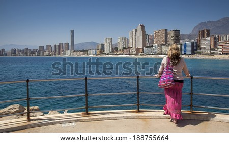 Beautiful female gazes over sea and beach towards Playa de Levante, Benidorm, Spain - travel photo under blue skies and sun.