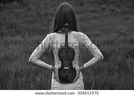 Beautiful female (girl, model) with big eyes and dark hair in a white dress playing the violin in the field and summer forest