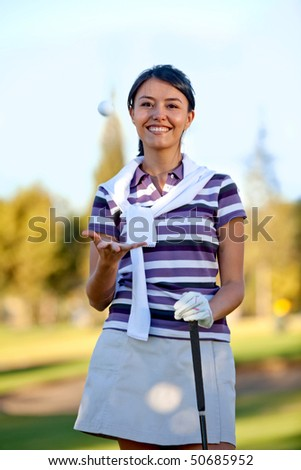 Beautiful female golf player at the course smiling
