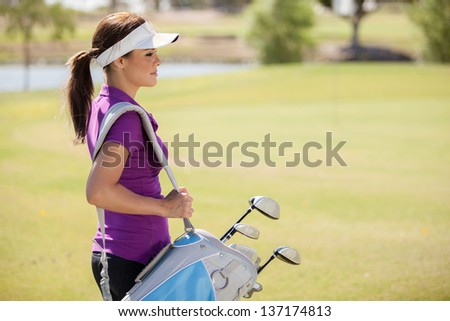 Beautiful female golfer carrying a golf bag and looking towards copy space