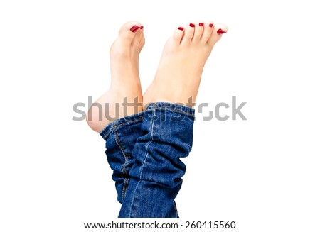 Beautiful female groomed feet with red nail polish in jeans closeup isolated on white background - stock photo