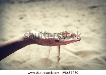 Beautiful female hand and the sand - stock photo