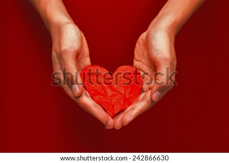Beautiful female hand holding the crumpled red paper heart - stock photo
