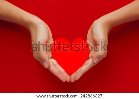 Beautiful female hand holding the red heart cut out of paper