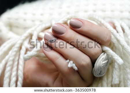 Beautiful female hand with beige nail design.  - stock photo