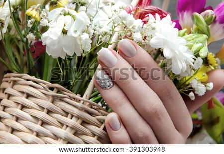 Beautiful female hand with beige nail design and flowers on background. - stock photo