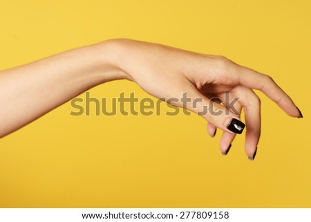 Beautiful female hand with neat manicure nails closeup on a yellow background copyspace, horizontal picture - stock photo
