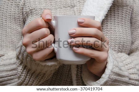 Beautiful female hand with warm beige nail design holdinbg a white cup. - stock photo