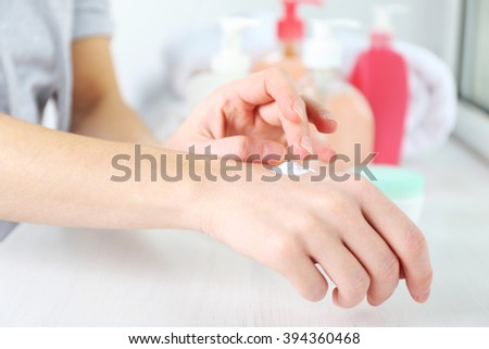 Beautiful female hands applying hand cream, close up - stock photo