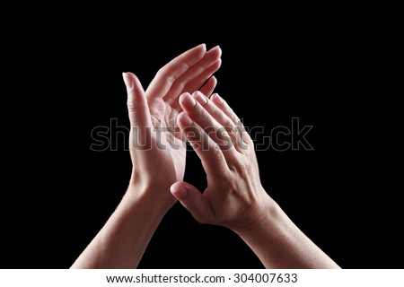 beautiful female hands isolated on black background giving applause