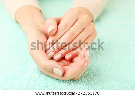 Beautiful female hands on fabric background - stock photo