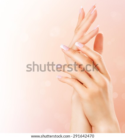 Beautiful Female Hands. Spa and Manicure concept. Woman hands with french manicure. Soft skin, skincare concept. Beauty nails. over beige background - stock photo