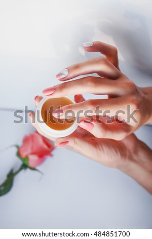 Beautiful female hands with a delicate pink manicure holding a jar of cream , wax , scrub. Manicure - Beautiful manicured woman's nails. Nail salon. Skin care and spa concept. hand cream