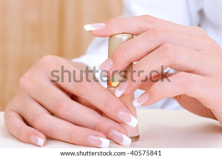 Beautiful female hands with beauty french manicure holding bottle enamel