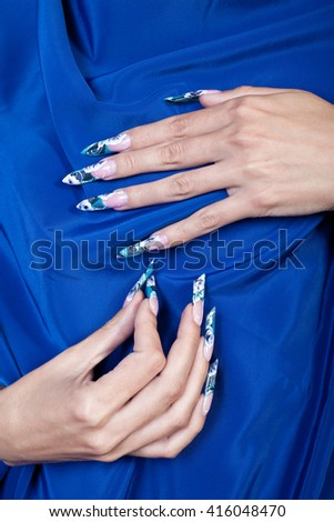 Beautiful female hands with blue flower manicure. - stock photo
