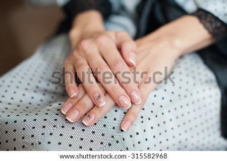 Beautiful female hands with manicure against a dress. - stock photo