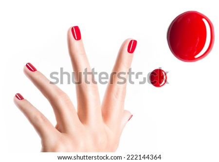 Beautiful female hands with red manicure and  drops of nail polish   - stock photo