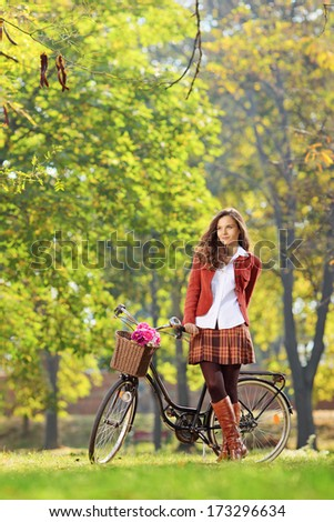 Beautiful female in a park with her bicycle - stock photo