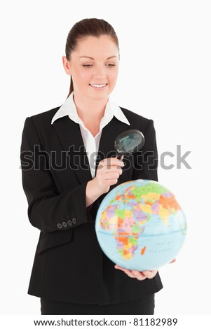 Beautiful female in suit holding a globe and using a magnifying glass while standing against a white background - stock photo