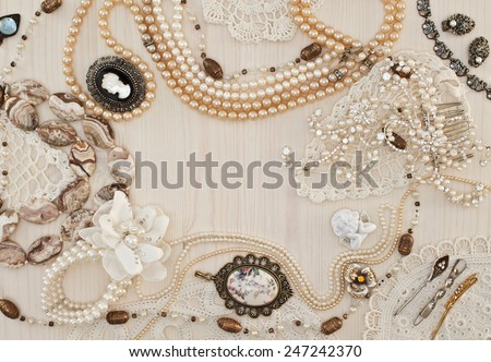 Beautiful female jewelry and trinkets on a light wooden background - stock photo
