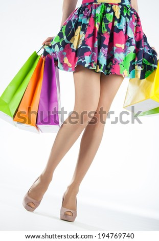 Beautiful female legs and multicolored shopping bags on white background - stock photo