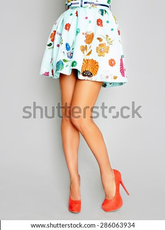 beautiful female legs in a skirt and heels.Young woman standing on one leg wearing high heels - stock photo