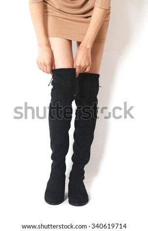 Beautiful female legs in black boots on a white background - stock photo