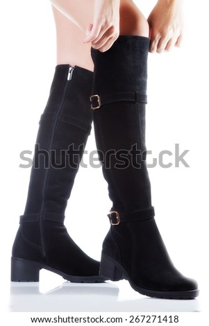 Beautiful female legs in black suede boots on a white background. hand tighten the boots - stock photo