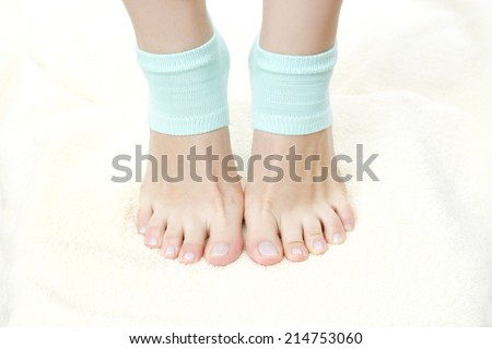 Beautiful female legs in blue socks. Foot care. Stand on tiptoes. - stock photo