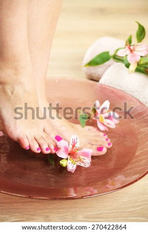 Beautiful female legs in bowl with water. Spa procedure concept