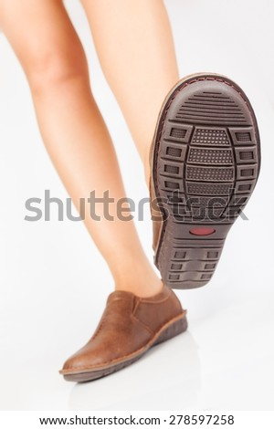 Beautiful female legs in brown, comfortable moccasins - stock photo