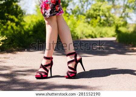 Beautiful female legs in pink shoes walking along the road